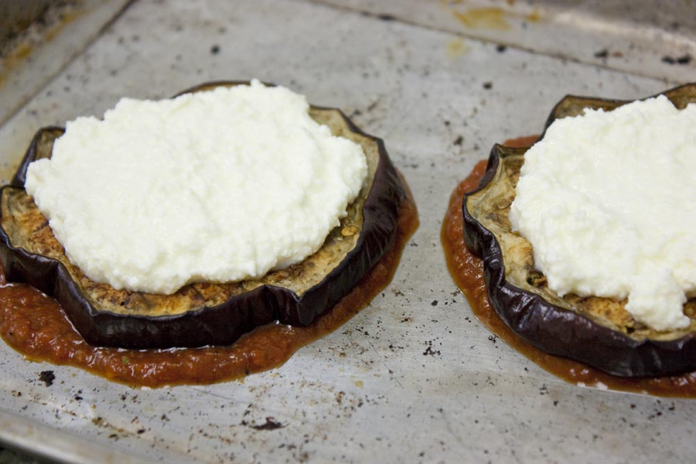 A thin layer of grass-fed ricotta cheese or fresh mozzarella cheese goes on top of the eggplant slices.