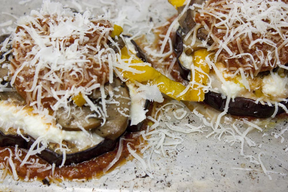 Grated grass-fed Parmesan cheese completes the first layer of the eggplant Parmesan.